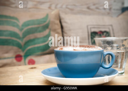 Cup and saucer of coffee on a wooden table in a rustic cafe - Stockfoto