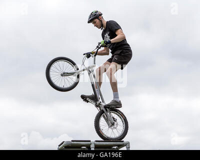 Stunt rider holding his stunt bike on the back wheel on a high platform - Stock Photo