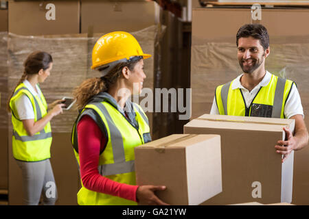 Portrait of workers are holding cardboard boxes and looking each other - Stock Photo
