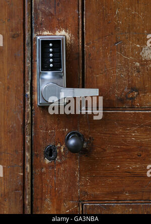 Simple door handle electronic lock with numeric buttons on old wooden door - Stock Photo