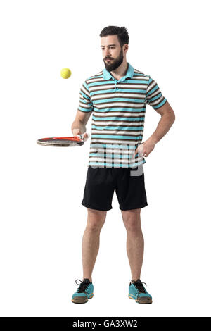 Relaxing tennis player in polo shirt bouncing ball with racket. Full body length portrait isolated over white studio - Stock Photo