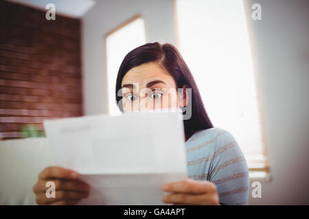Shocked woman reading letter - Stock Photo