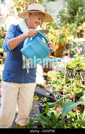 Happy gardener spraying water on plants at garden - Stock Photo