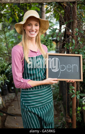 Portrait of happy gardener with open text on chalkboard at garden - Stock Photo