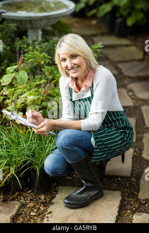 Happy woman writing on clipboard while examining plants - Stock Photo
