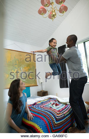 Father lifting flying daughter over bed in bedroom - Stockfoto