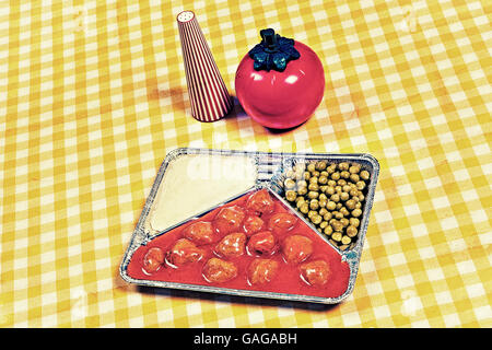TV dinner tray vintage retro meal aluminum dish on tablecloth with tomato sauce - Stock Photo