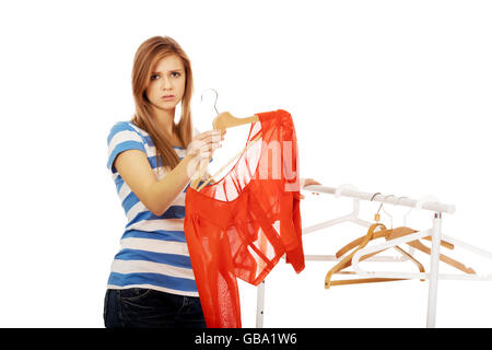 Teenager standing next to empty hanger and holding only blouse - Stock Photo