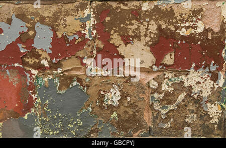Multi-coloured distressed peeling paint on a derelict wall - Stock Photo