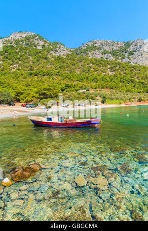 Traditional fishing boat in sea bay on secluded beach, Samos island, Greece - Stock Photo
