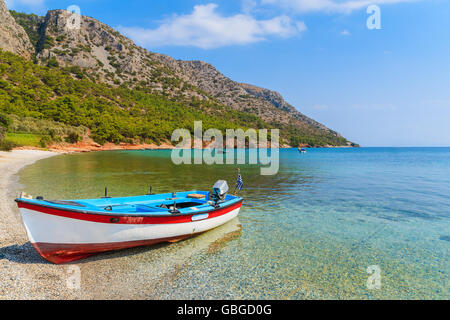 Traditional Greek fishing boat in sea bay on secluded beach, Samos island, Greece - Stock Photo