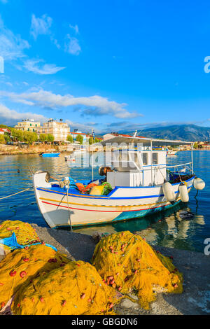 Traditional Greek fishing boat mooring in port at sunset time on Samos island, Greece - Stock Photo