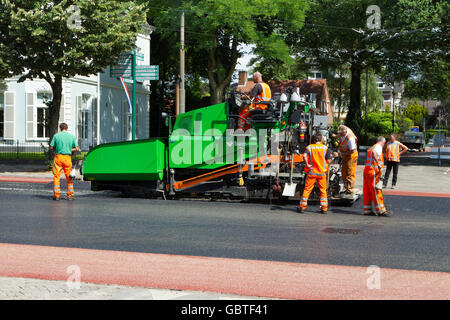construction workers laying tarmac tarmacadam asphalt - Stock Photo
