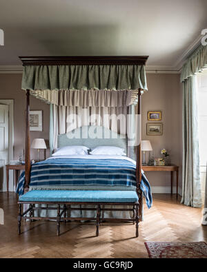 Four poster bed in bedroom with parquet flooring and antique bench with blue cushion. The indigo throw is West African - Stock Photo