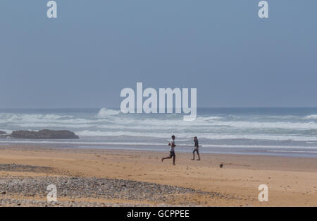 Two Young Men playing football on a beach, with waves in the background. - Stock Photo