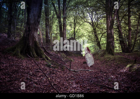 Woodland fantasy photography: a young red haired redhead woman girl wearing a long flowing dress walking down  a - Stockfoto