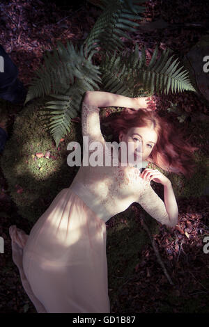 Woodland fantasy photography: a young red haired redhead woman girl wearing a long flowing dress lying down alone - Stockfoto