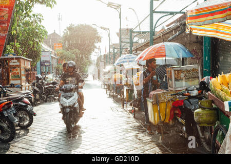Kuta, Indonesia - March 08, 2016: Indonesian food vendor hides from the rain under umbrella of his stall on the - Stock Photo