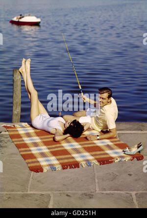 1950s 1960s couple man woman sitting on porch in rocking for Rocking fishing rod