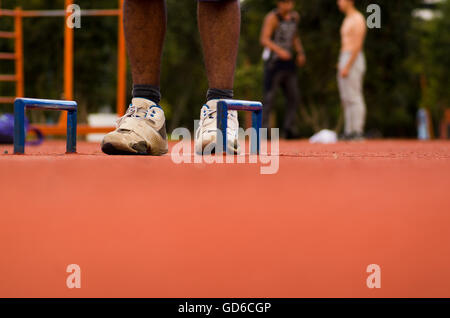 White shoes with mans legs standing on orange athletic running surface between two florr mounted blue handles, blurry - Stock Photo