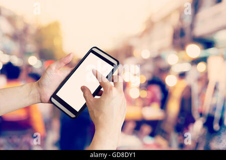 Hand using smartphone and Blurred crowd of people walking through a city street. vintage toned photo. - Stock Photo
