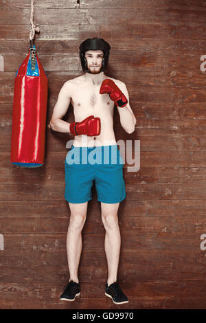 Top view photo of handsome young sportsman on wooden floor. Man with boxing gloves and punching bag - Stock Photo