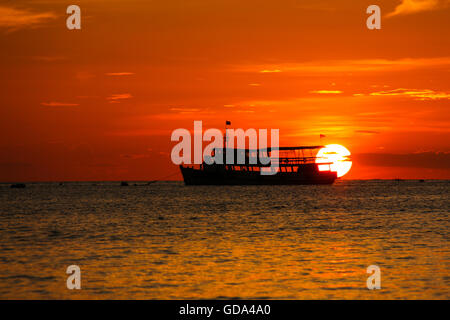 sunset on the beach with fishing boat in Pattaya, Thailand - Stock Photo