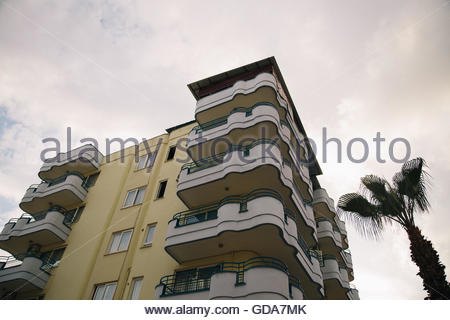 Palm tree tops against apartment or hotel building and blue sky. Vacation tropical background. - Stock Photo