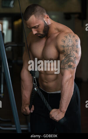 Big Man In The Gym Is Exercising Tricpes On Machine - Muscular Athletic Bodybuilder Model Exercise In Fitness Center - Stock Photo
