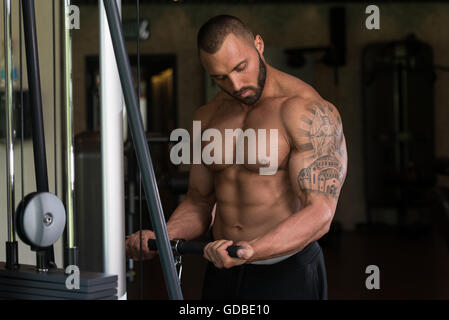 Big Tattooed Man In The Gym Is Exercising Biceps On Machine - Muscular Athletic Bodybuilder Model Exercise In Fitness - Stock Photo
