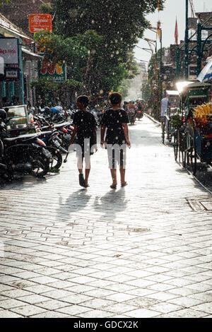 Kids walk under the sun shower on the street of Kuta, Bali, Indonesia on March 08, 2016 - Stock Photo