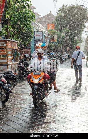 Indonesian man riding a motorbike under the rain on the street of Kuta, Bali, Indonesia. - Stock Photo