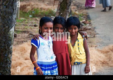 Unidentified three Indian girls on the street in fishing village. Kovalam. Kerala. India - Stock Photo