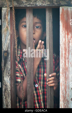 Unidentified Indian boy looks through a window at home in small fishing village - Stock Photo