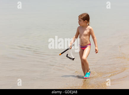Girl walking out of sea carrying, snorkel and mask - Stock Photo