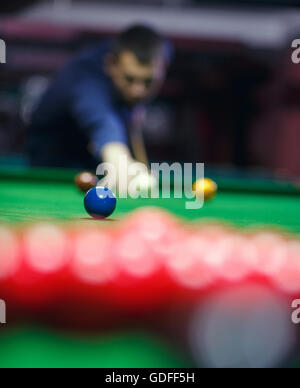 young man lines up his shot as he breaks the balls for  start  game of billiards - Stock Photo