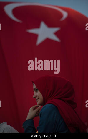 Muslim woman wearing red headscarf with Turkish flag Istanbul Turkey - Stock Photo