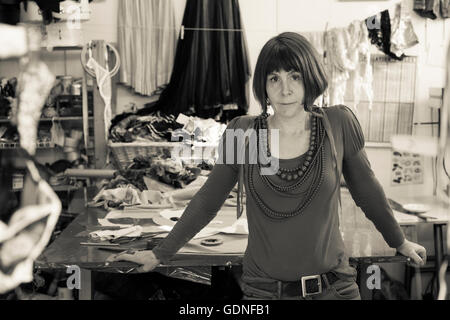 A monochrome image of a woman standing in a dressmaker's shop. - Stock Photo