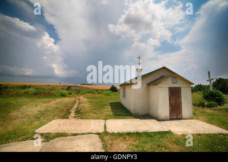 Landscape - Small lonely church on cloudy the sky a background. - Stock Photo