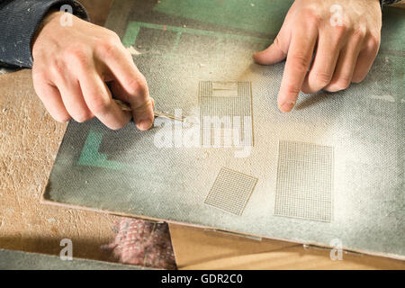 Hand picking a tiny metal grill up for scale model buildings using a pair of pincers - Stock Photo