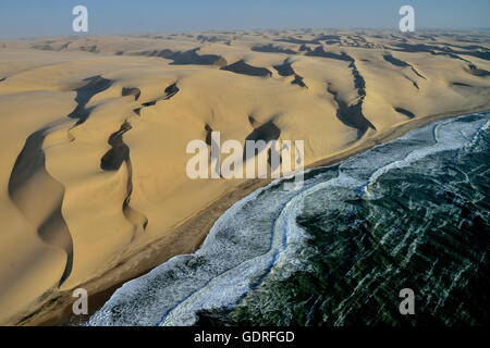 Aerial view, dunes in Namib desert, Atlantic Ocean, waves breaking on Namibian coast south of Sandwich Harbour - Stock Photo