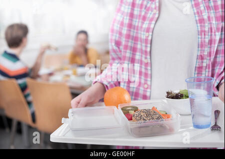Midsection of a university student with lunch in canteen, Bavaria, Germany - Stock Photo