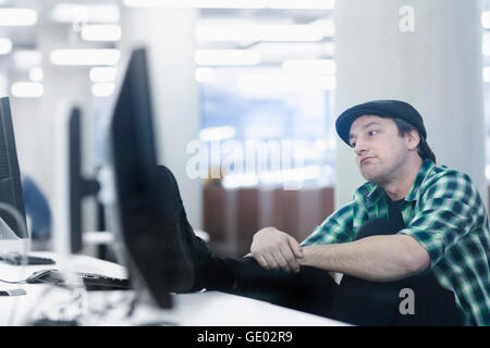 Mid adult man sitting in the office and thinking, Freiburg im Breisgau, Baden-Württemberg, Germany - Stock Photo