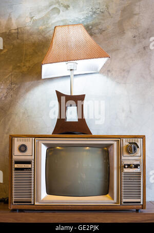 retro tv with wooden case and lantern in room with vintage wallpaper on wood table - Stock Photo