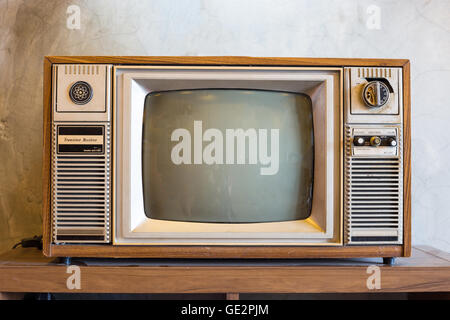 retro tv with wooden case in room with vintage wallpaper on wood table - Stock Photo