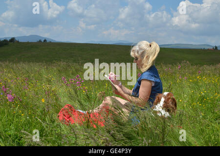 Woman with dog relaxing on a meadow surrounded with pink flowers and writing something in her notepad, on windy - Stockfoto