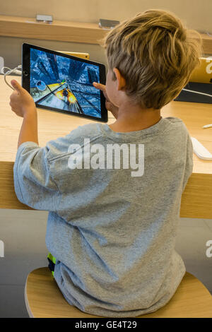 A young boy 7-8 years old plays a game on an iPad at the Apple Store in Santa Barbara, California. - Stock Photo