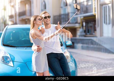 Man and woman taking selfie near car - Stock Photo