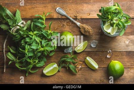 Ingredients for making mojito summer cocktail. Fresh mint bunch and leaves, limes, spoon of brown sugar, ice over - Stock Photo