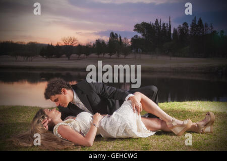 Bride and groom kiss under a spectacular sunset sky lying on the grass - Stock Photo